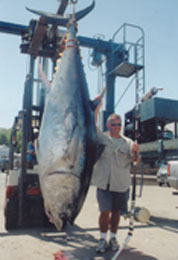 man next to huge tuna